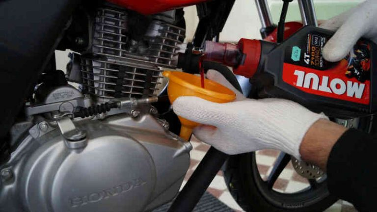 Man putting engine oil in a motorcycle